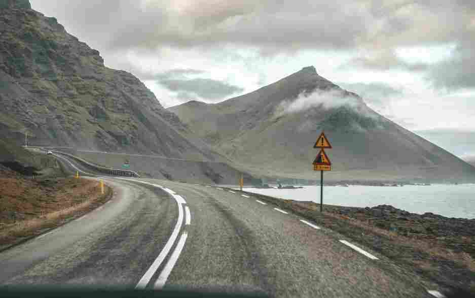 Estrada sinuosa beirando o mar na costa leste da Islândia